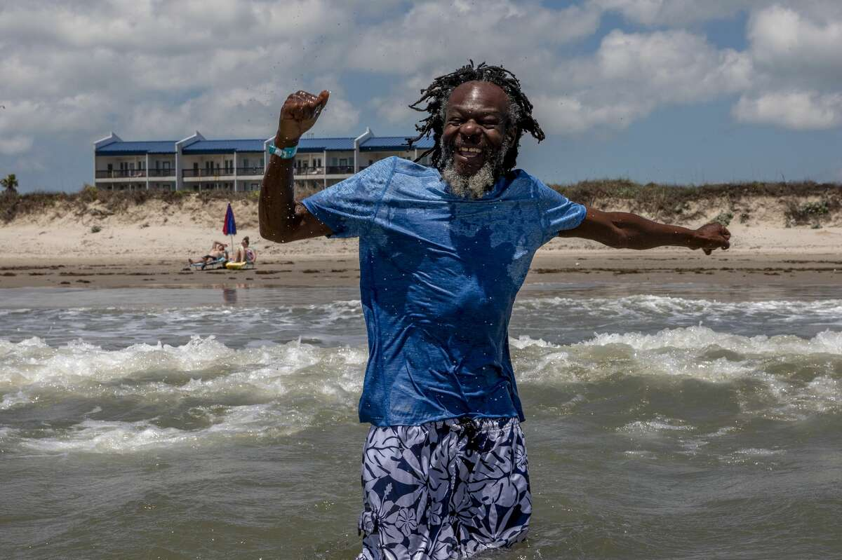 Neville punches the air with delight after being splashed by a large wave at the beach at Corpus Christi. Neville, who normally sleeps in boxes in a little nook downtown, was brought to Corpus Christi by a group of three homeless outreach workers to see if he could handle public transportation. The outreach workers are trying to reconnect him to his family in Zimbabwe.
