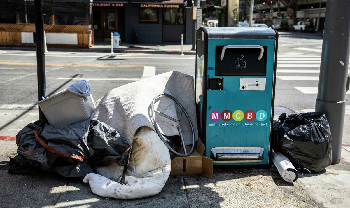 Debris piles up next to a smart trash receptacle on Fifth Street in San Francisco.