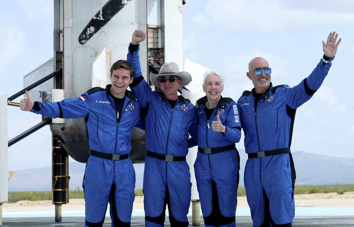 Blue Origin's New Shepard crew, from left, Oliver Daemen, Jeff Bezos, Wally Funk, and Mark Bezos pose for a picture near the booster after flying into space in the Blue Origin New Shepard rocket on July 20, 2021 in Van Horn, Texas.