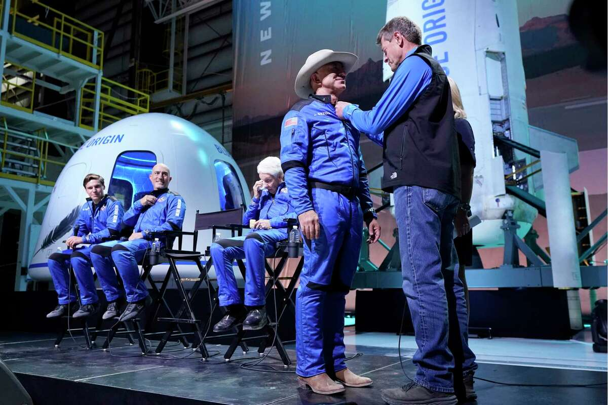 Oliver Daemen, from left, Mark Bezos and Wally Funk, look on as Jeff Bezos, second from right, is awarded his Blue Origin made astronaut wings by former NASA astronaut, Jeff Ashby, right, who is now based with Blue Origin, during a New Shepard post launch briefing at the spaceport near Van Horn, Texas, Tuesday, July 20, 2021.