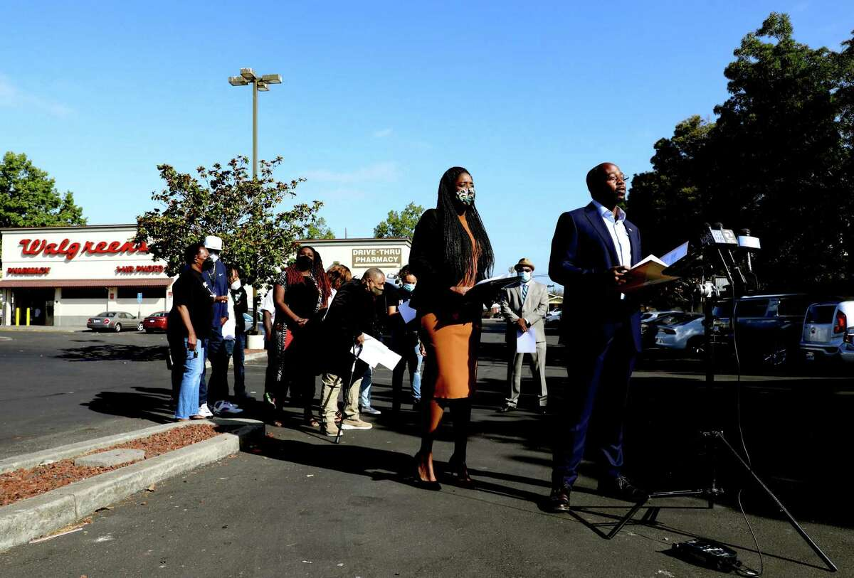 East Oakland City Council Member Loren Taylor (right) speaks during a press conference at an East Oakland Walgreens. Taylor, fellow Council Member Treva Reid (orange dress) and local residents are imploring Walgreens not to shut its doors at one of the few places where residents can buy groceries.