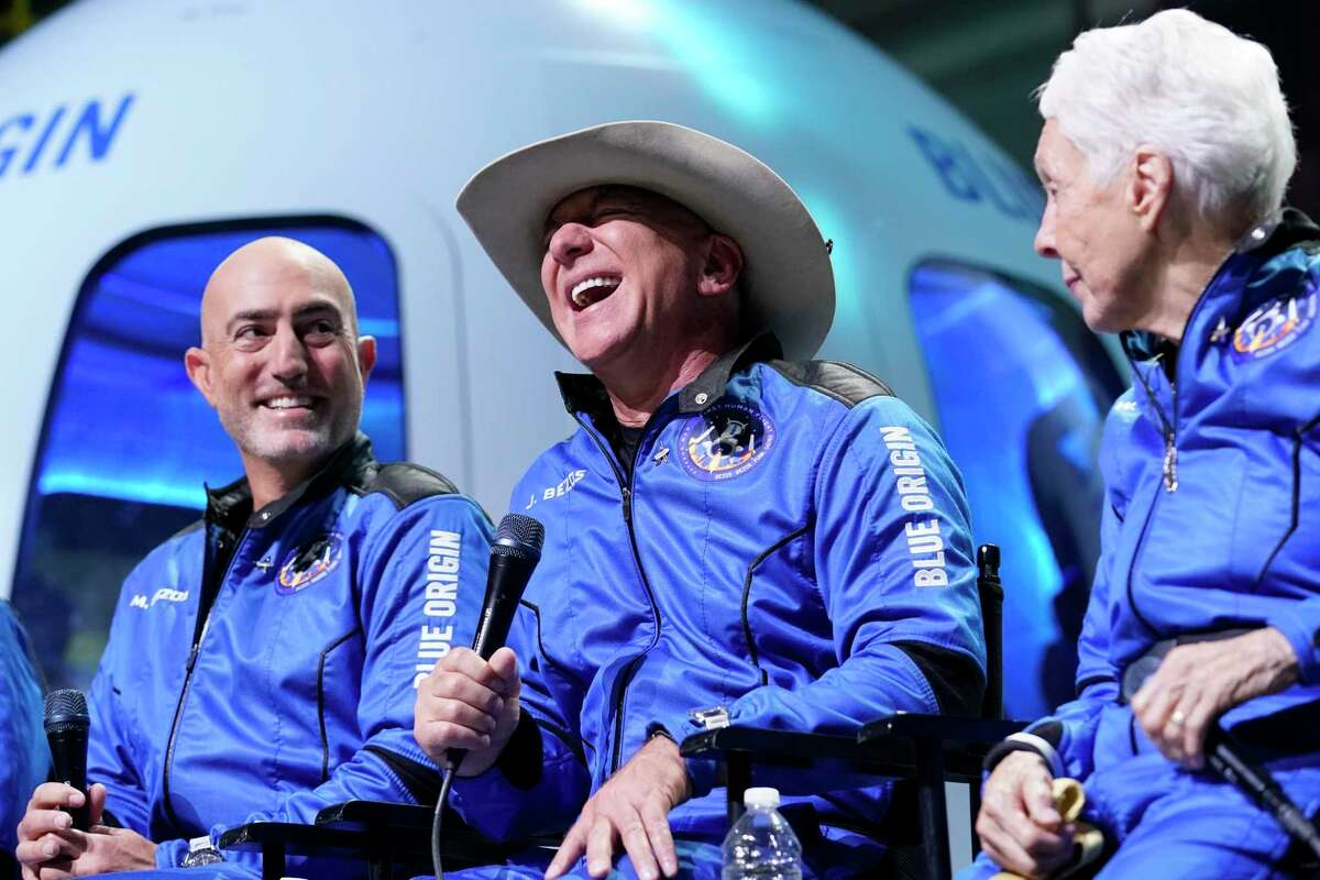 Mark Bezos, left, and Wally Funk, right, listen as Jeff Bezos, center, founder of Amazon and space tourism company Blue Origin makes comments about their flight experience during a post launch briefing at its spaceport near Van Horn, Texas, Tuesday, July 20, 2021. (AP Photo/Tony Gutierrez)
