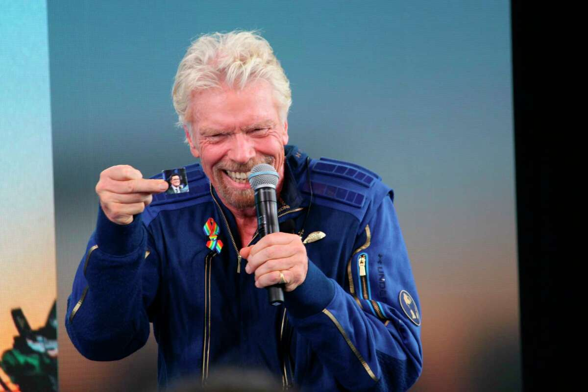 """Richard Branson holds up a photograph of CBS """"Late Show"""" host Stephen Colbert during a news conference after Branson and five crewmates from his Virgin Galactic space-tourism company reached the edge of space following a launch near Truth or Consequences, N.M., on Sunday, July 11, 2021. Colbert served as master of ceremonies for the launch from Spaceport America. (AP Photo/Susan Montoya Bryan)"""
