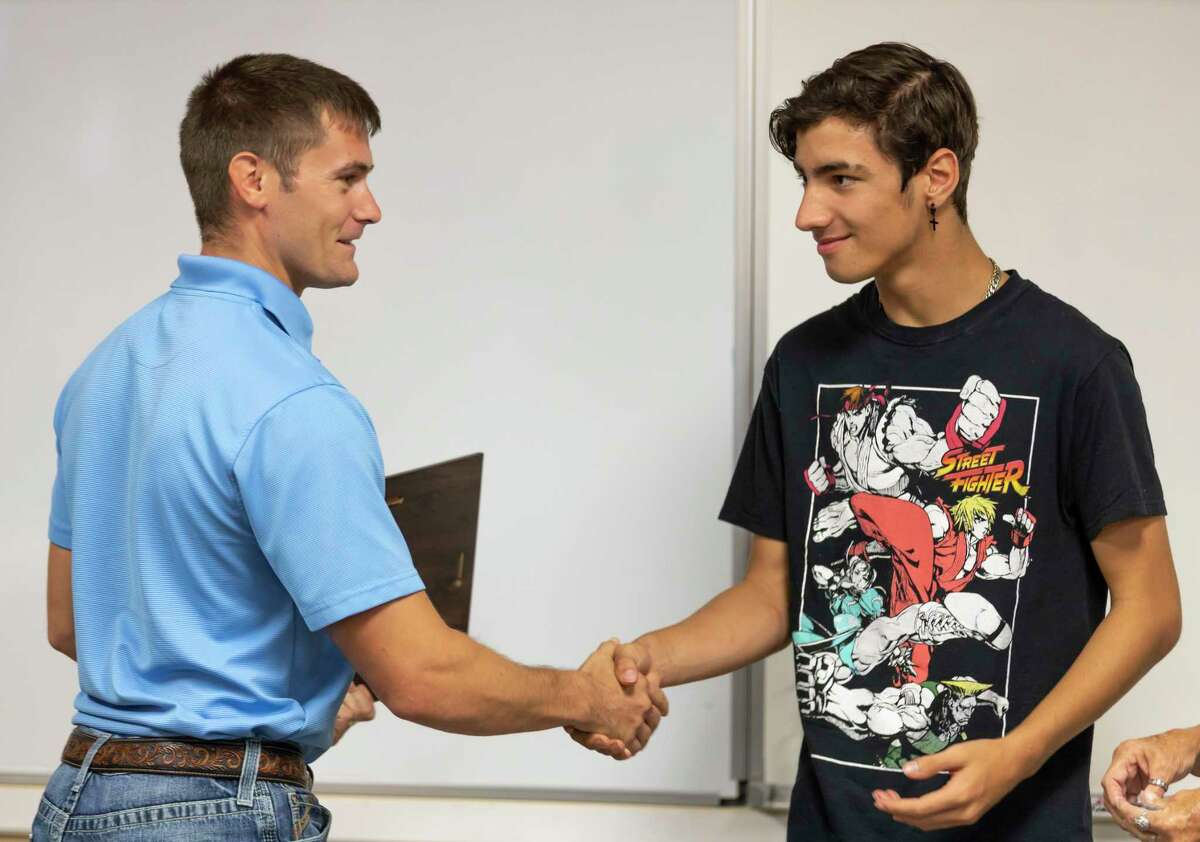 Brandon Hayden, left, shakes hands with 17-year-old Logan Dillard during a reunion between Dillard and the first responders who assisted him at the East Montgomery County Fire Department - Station 151, Thursday, July 22, 2021, in New Caney. Dillard was electrocuted when a metal pole he was carrying struck a power line and was later revived after MCHD medics and East Montgomery County firefighters performed CPR before being transported to the hospital.