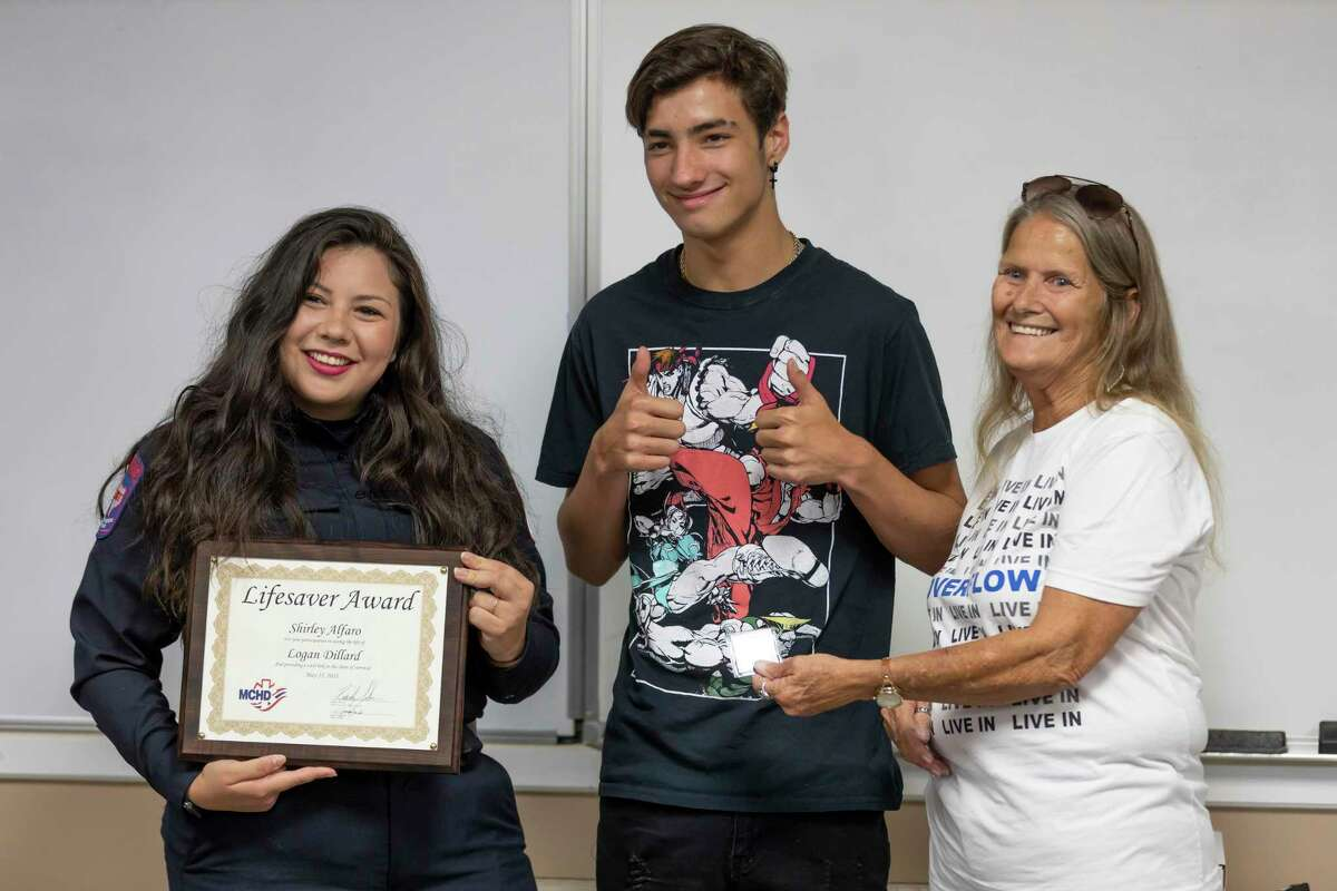 Shirley Alfaro, left, poses for a portrait with 17-year-old Logan Dillard, center with his grandmother, Sharon Scruggs, during a reunion between Dillard and the first responders who assisted him at the East Montgomery County Fire Department - Station 151, Thursday, July 22, 2021, in New Caney. Dillard was electrocuted when a metal pole he was carrying struck a power line and was later revived after MCHD medics and East Montgomery County firefighters performed CPR before being transported to the hospital.