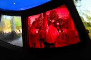 Couples socialize outside as seen through one of the signature round stained glass windows during Heritage Happy Hour Thursday at the McFaddin-Ward House Museum's carriage house. Photo made Thursday, July 22, 2021 Kim Brent/The Enterprise