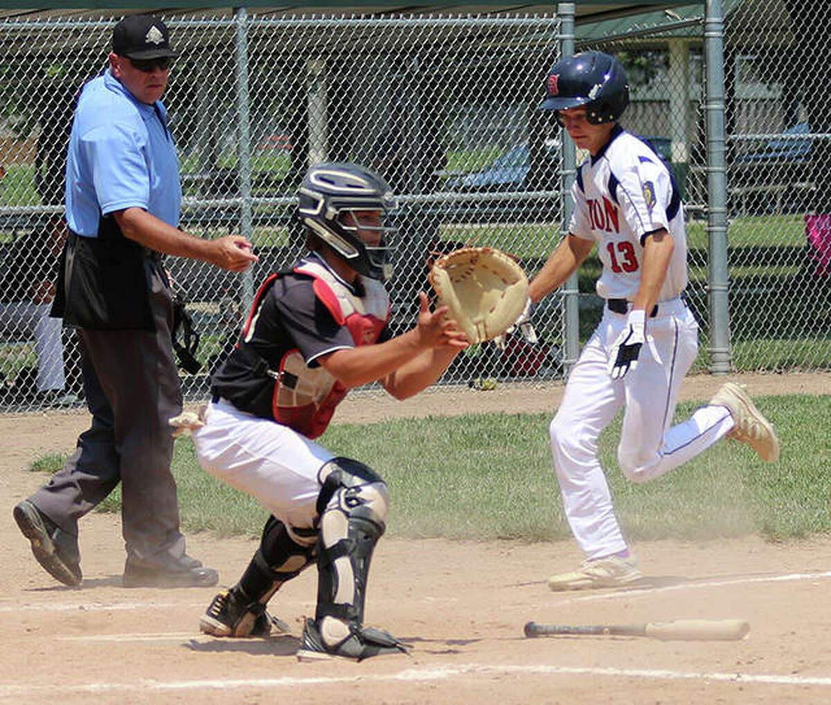 Alton's Austin Callovini (right) scored the winning run in the bottom of the seventh inning in Thursday night's 6-5 victory over Trenton in a Fifth Division American Legion baseball tournament game in Centralia. He is shown scoring in a Firecracker Tournament game earlier this season.