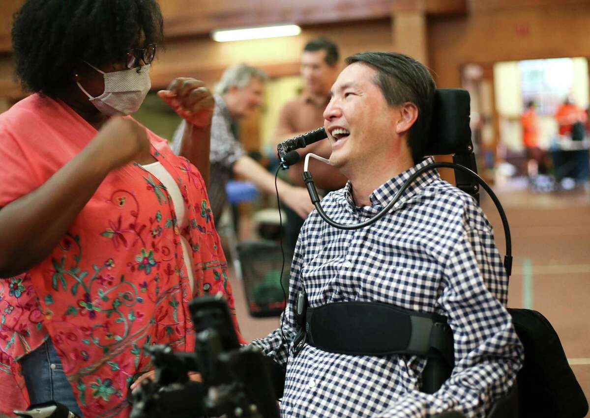 """Dr. Rex Marco shares a laugh with his former caregiver Olivia Garrett during his """"Dr. Marco's Alive Day"""" in Houston on Wednesday, July 21, 2021. Dr. Marco, a spine surgeon and musculoskeletal oncologist, was paralyzed in a mountain bike accident in 2019."""