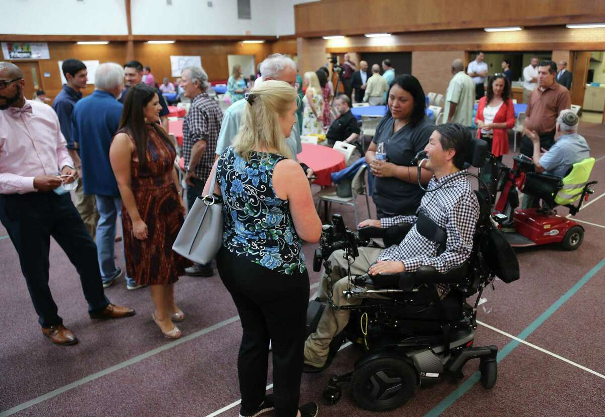 """Dr. Rex Marco, talks to friends and family at his """"Dr. Marco's Alive Day"""" in Houston on Wednesday, July 21, 2021. Dr. Marco, a spine surgeon and musculoskeletal oncologist, was paralyzed in a mountain bike accident in 2019."""