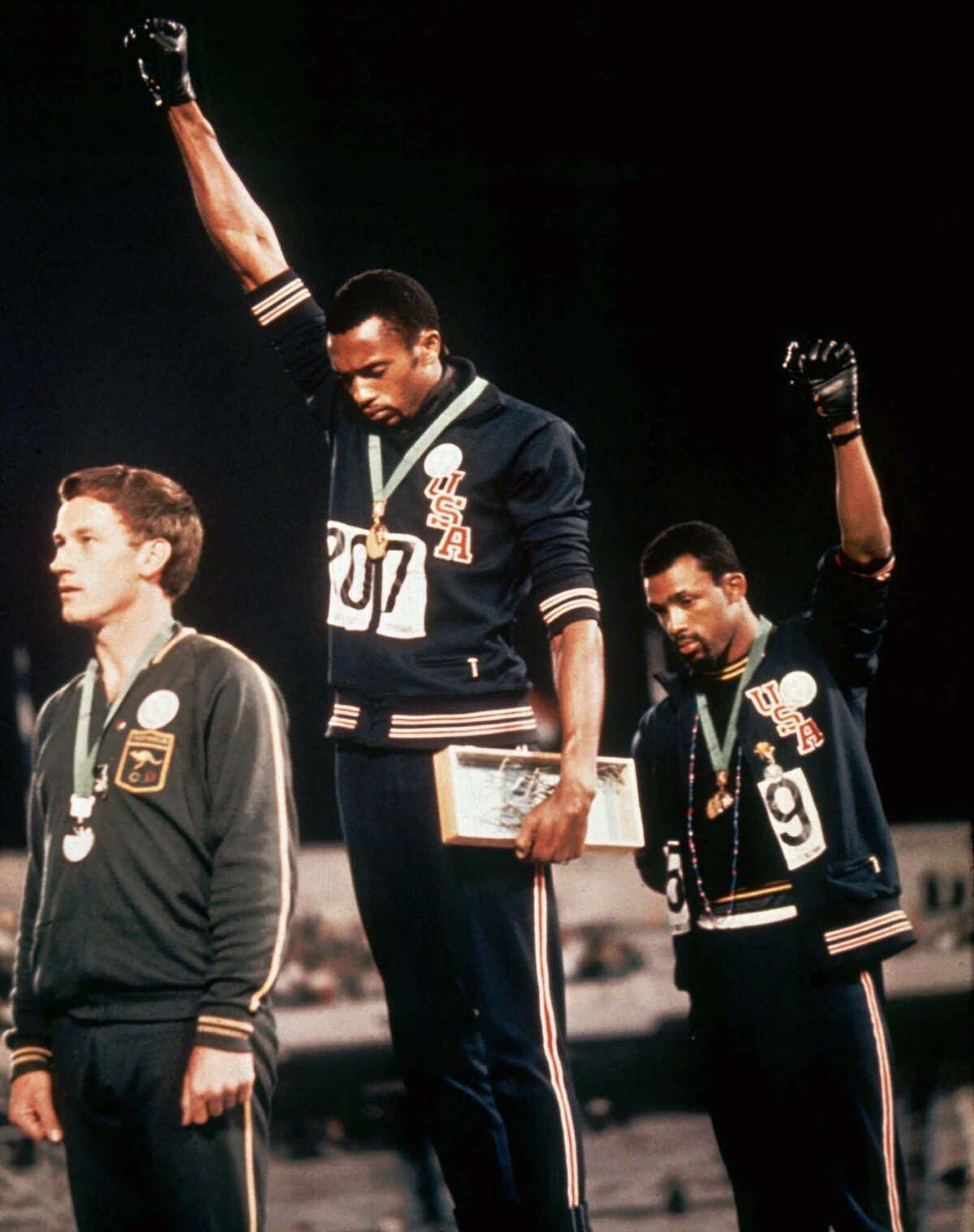 Tommie Smith, center, and John Carlos raise their firsts to protest racial injustice while on the medal podium at the 1968 Summer Olympics in Mexico City.