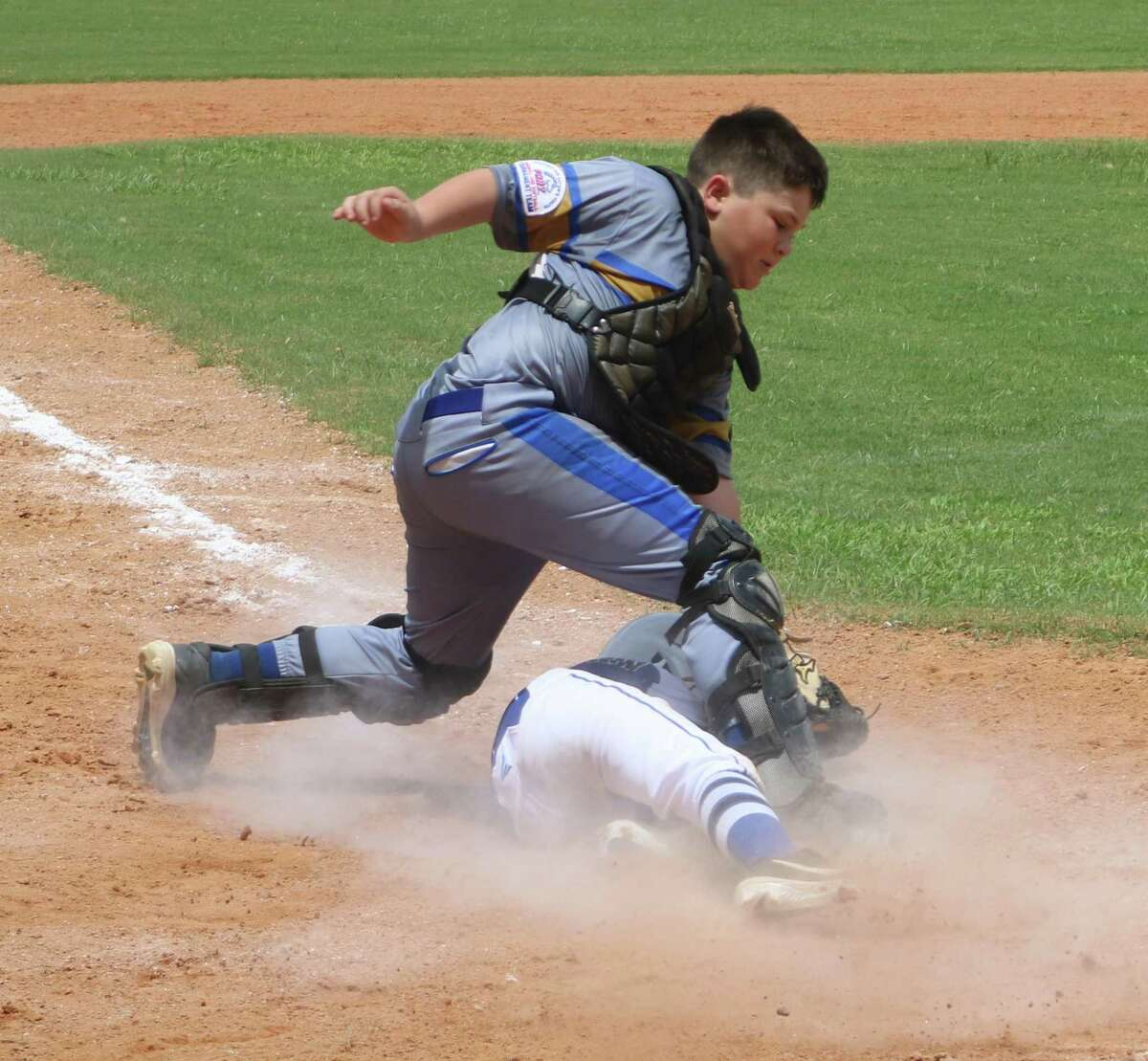 A Friendswood player slides under the PYBSA catcher for a run that helped give the team a 10-3 advantage Thursday.