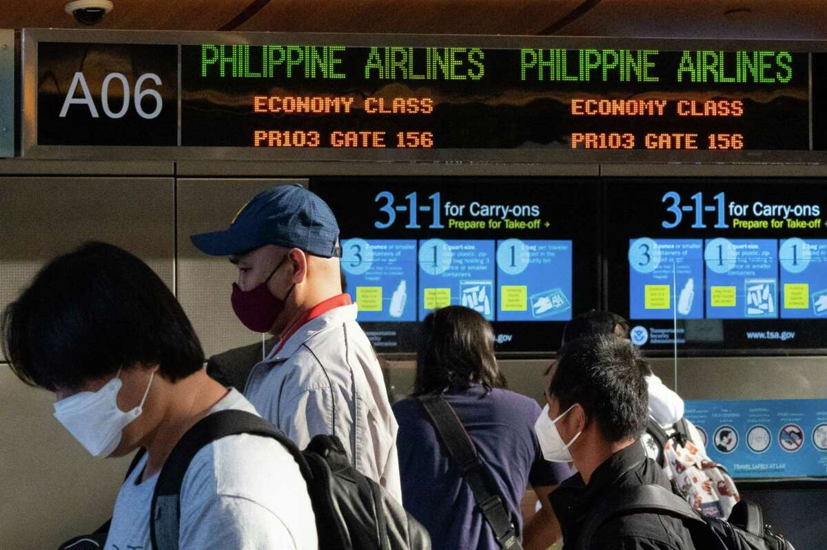 Travelers wearing protective masks queue at the Philippine Airlines at Los Angeles International Airport in Los Angeles on May 28, 2021.