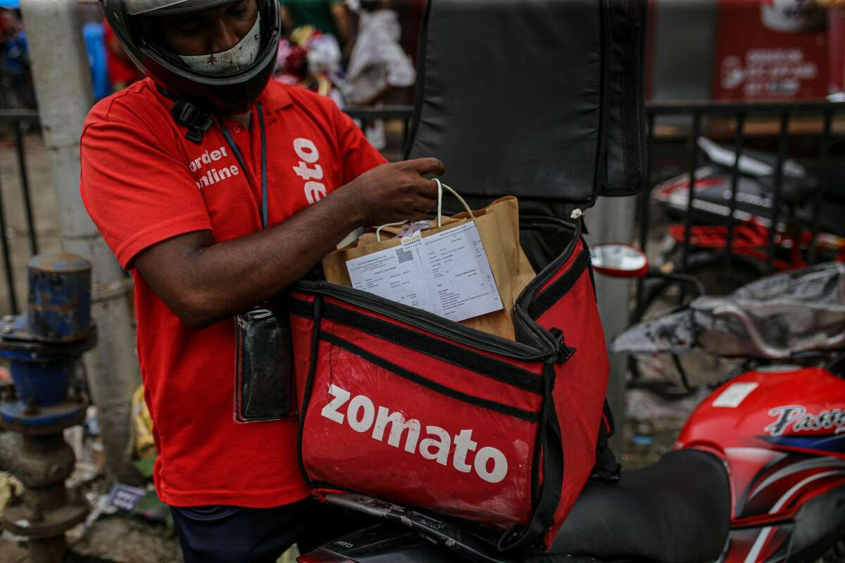 A Zomato Ltd. delivery rider packs an order into a delivery bag in Mumbai, India, on Friday, July 16, 2021. Zomato $1.3 billion initial public offering was fully subscribed on the first day of sale, after anchor funds including BlackRock Inc. bid for 35 times more stock than was offered to them.