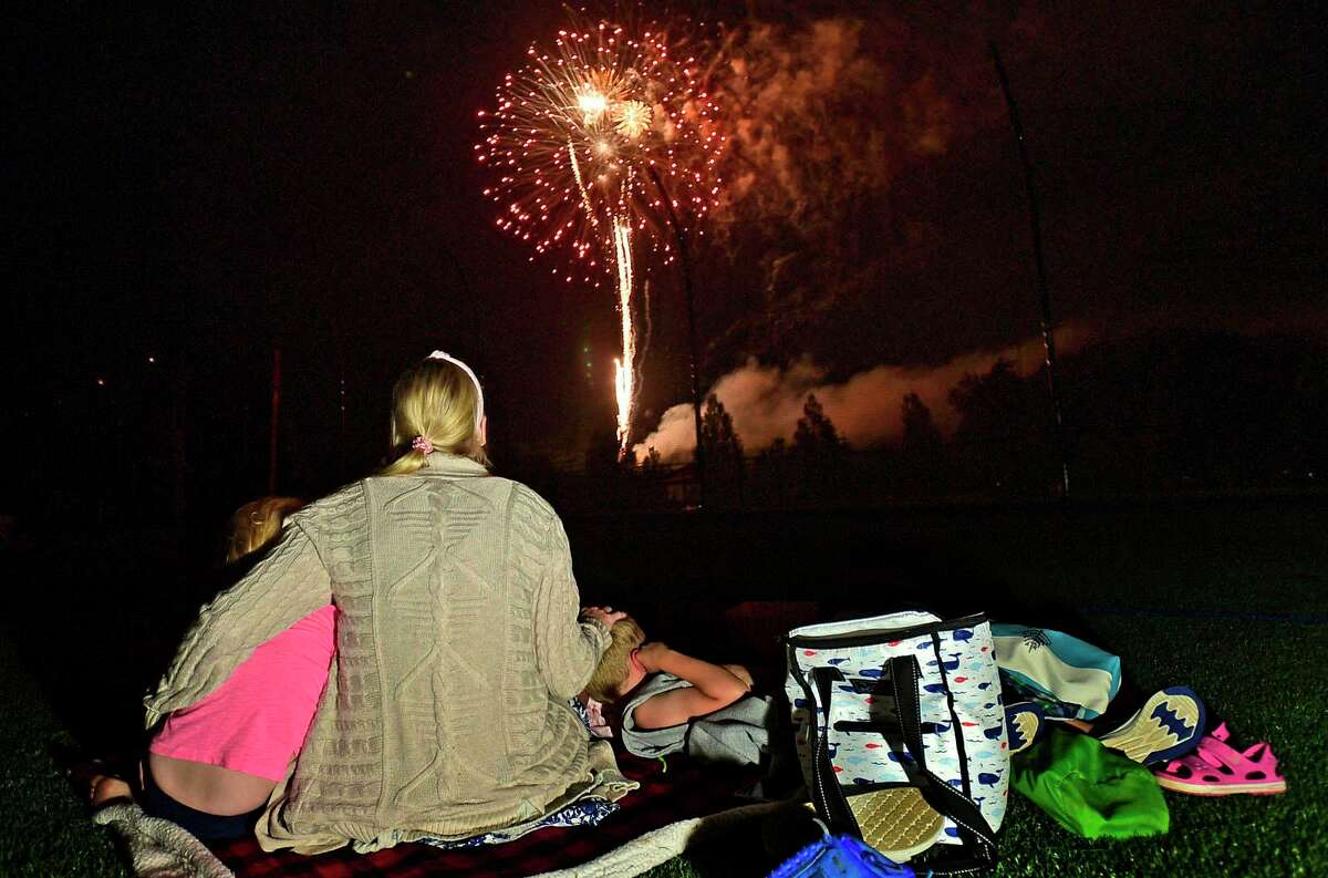 The Lafreniere family enjoy the Darien 2021 Fireworks Display at Darien High School Thursday, July 23, 2021, in Darien, Conn. Last year's display was cancelled due to the pandemic.