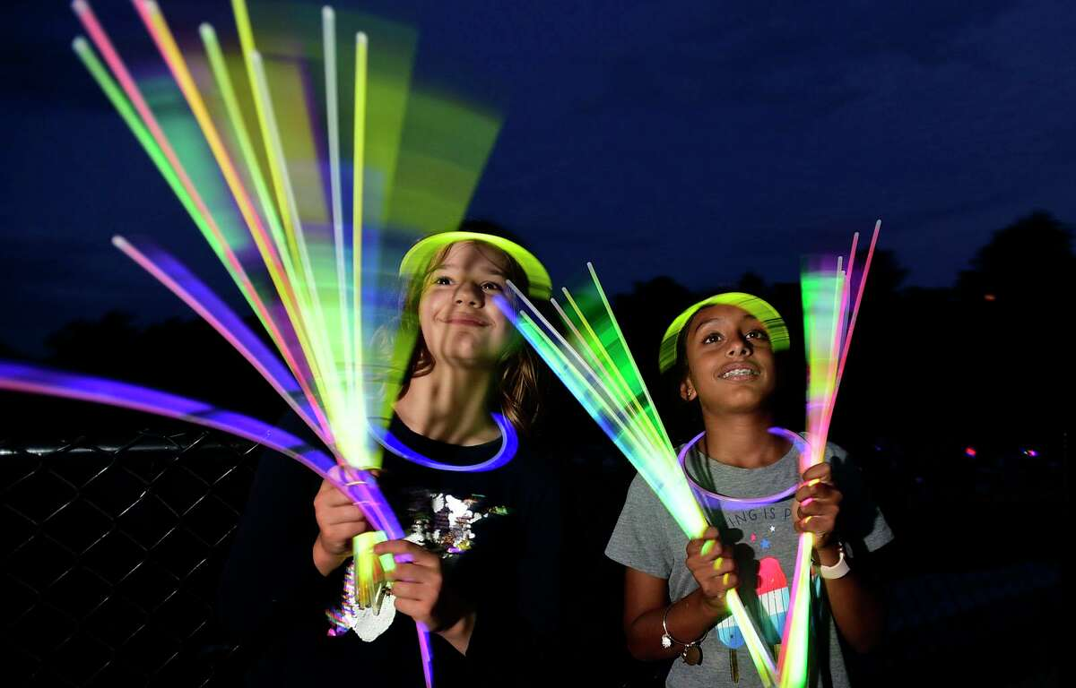 Residents Dorothy Den Dooven and Neera Arjunan, both 10, enjoy the Darien 2021 Fireworks Display at Darien High School Thursday, July 23, 2021, in Darien, Conn. Last year's display was cancelled due to the pandemic.