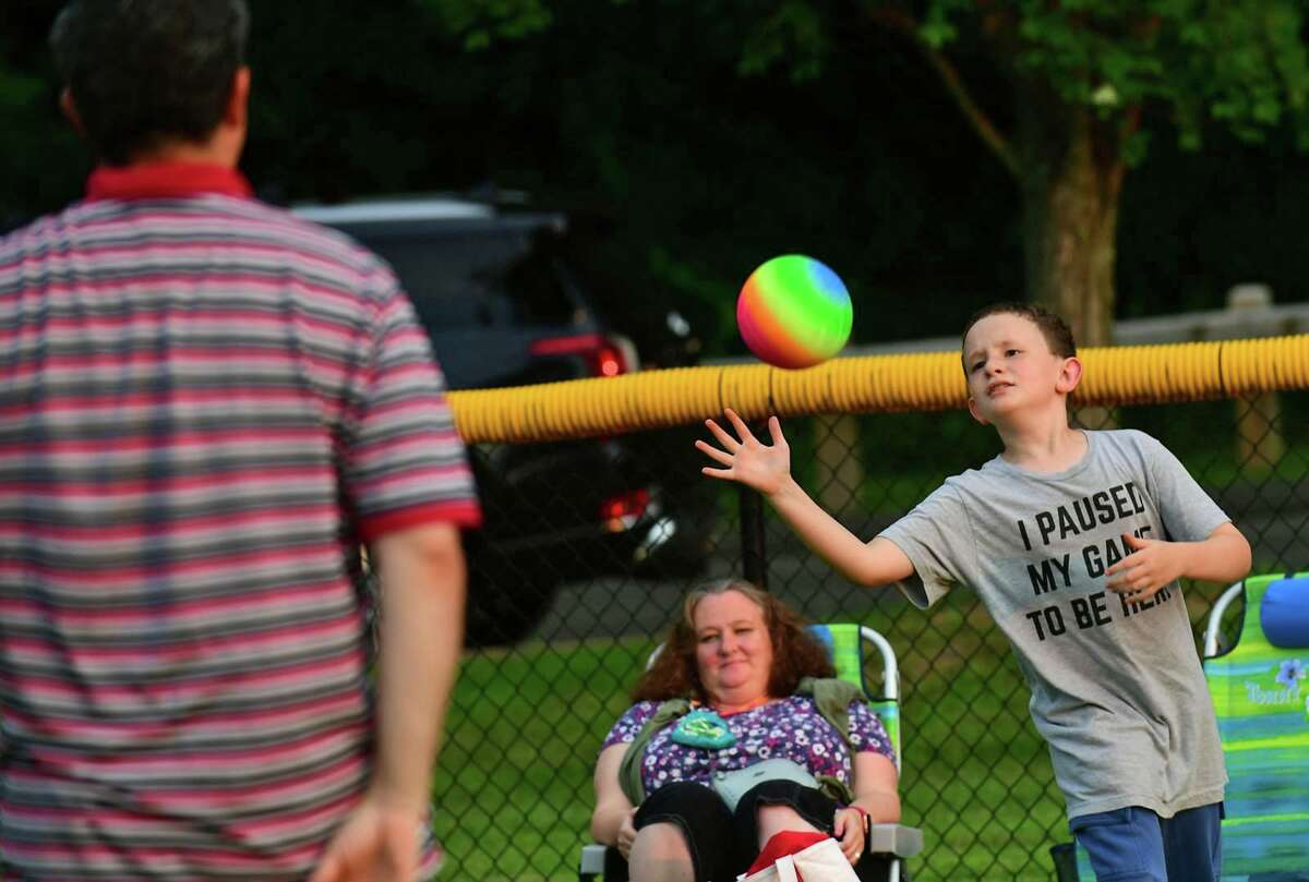 Jason Golden plays catch with his family at the Darien 2021 Fireworks Display at Darien High School Thursday, July 23, 2021, in Darien, Conn. Last year's display was cancelled due to the pandemic.