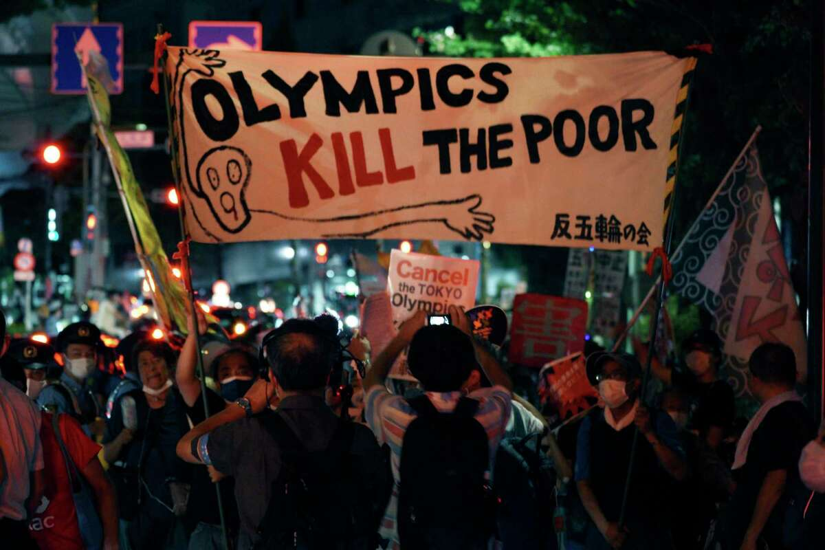 Anti-Olympic protestors demonstrate near the National Stadium in Tokyo, Japan where the opening ceremony of the Tokyo Olympics is taking place, Friday, July 23, 2021. (AP Photo/Kantaro Komiya)
