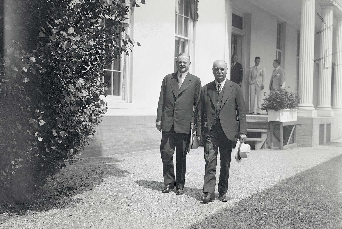 President Hoover and Vice President Charles Curtis walk outside the White House.