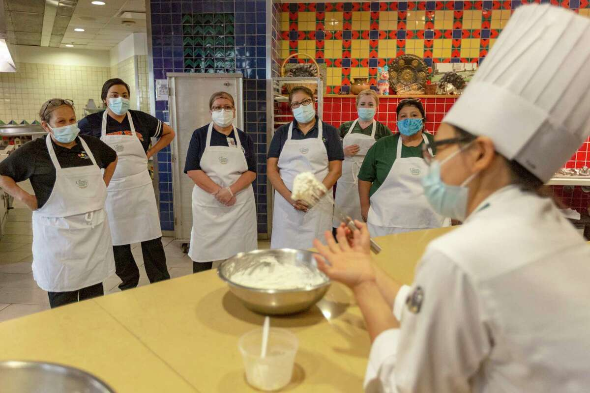 San Antonio Independent School District cooks watch Wednesday, July 21, 2021, at the Culinary Institute of America as CIA faculty chef Uyen Pham talks about piping whipped cream. The SAISD employees were at the CIA for a day-long training program to help develop their kitchen organization abilities and their food preparation and knife skills among other things.