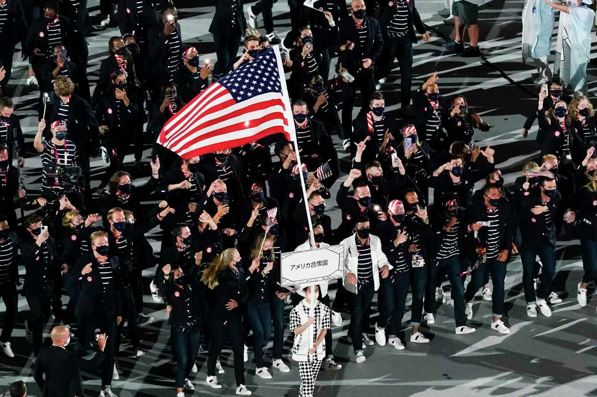 Sue Bird and Eddy Alvares, of the United States of America, carry their country's flag during the opening ceremony at the Olympic Stadium at the 2020 Summer Olympics, Friday, July 23, 2021, in Tokyo.