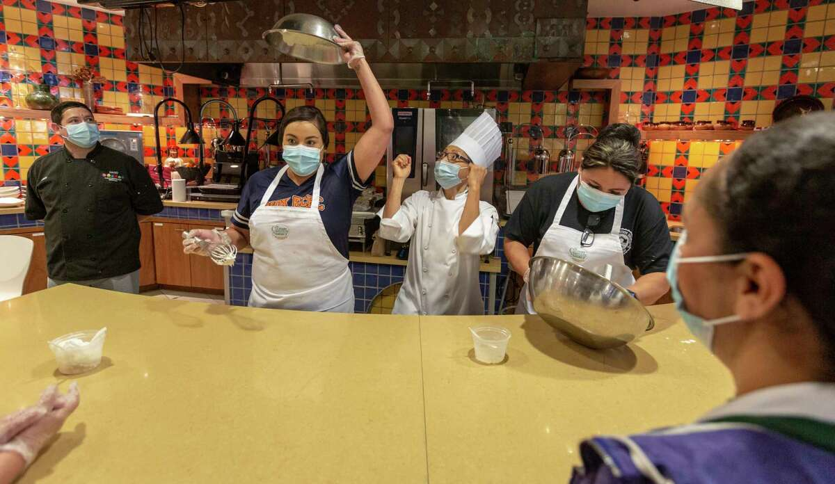Disney Maldonado holds freshly whipped cream over her head Wednesday, July 21, 2021, as Culinary Institute of America faculty chef Uyen Pham, center, cheers during a contest to see who can make whipped cream the fastest. Maldonado, a San Antonio Independent School District cook, was at the CIA for a day-long training program designed to help the food services employees to develop their kitchen organization abilities and their food preparation and knife skills among other things.