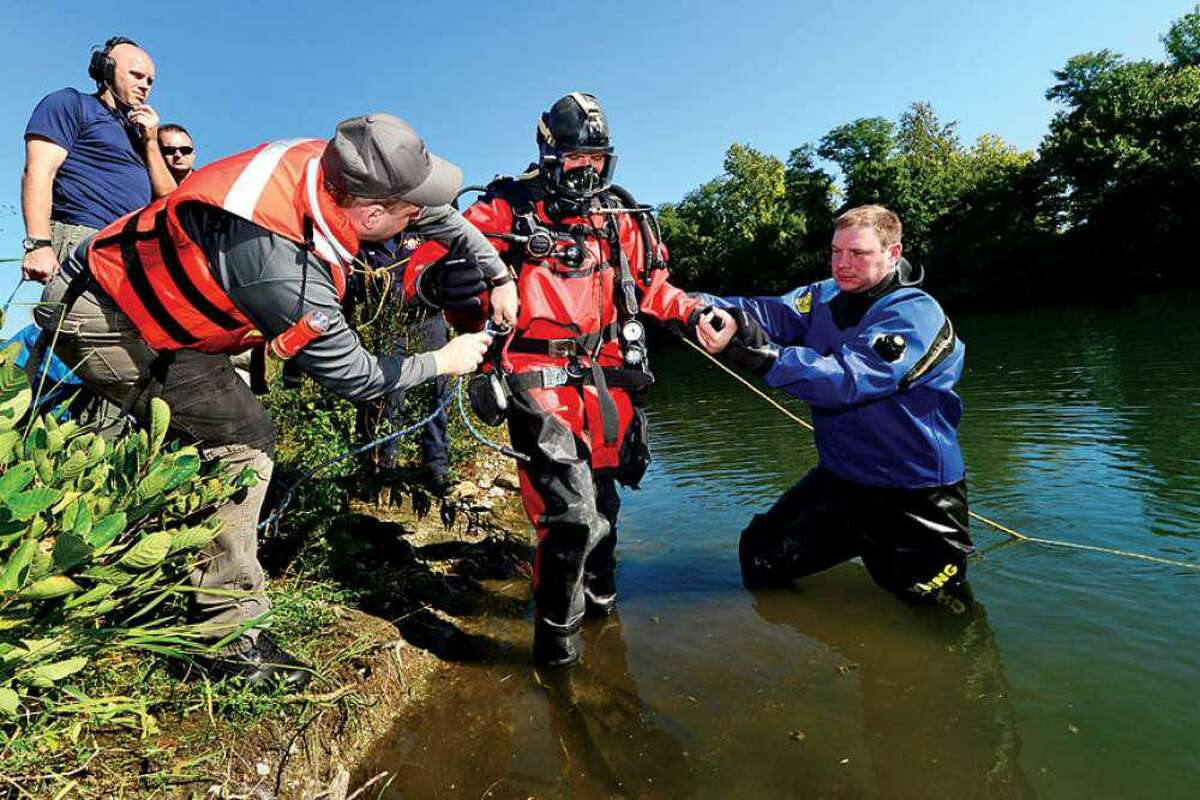 Members of Wilton and Westport's police and fire departments conduct a water rescue training with their dive teams in Wilton in 2014. On Tuesday night Wilton's Board of Selectmen voted unanimously to disband its small group of personnel who are trained for underwater work.