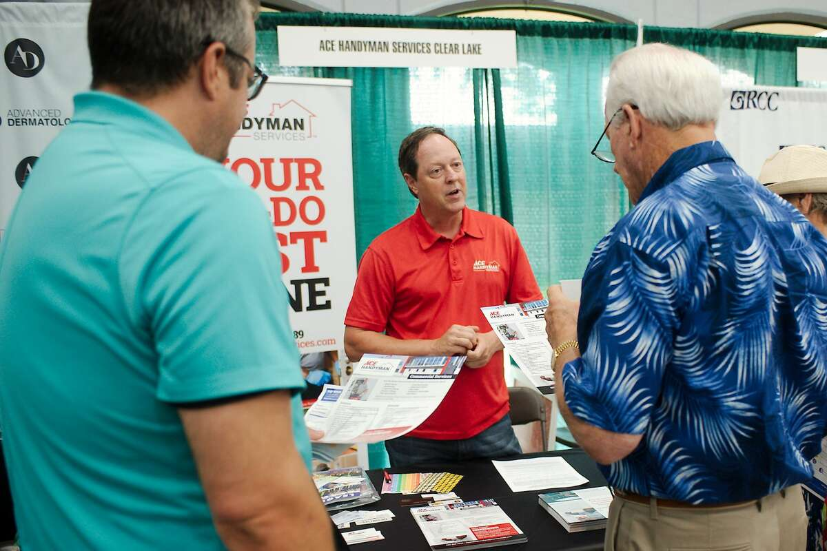 Pastor Rob Bailey and Ron Willis chat with Larry Millican at the Ace Handyman Services booth.