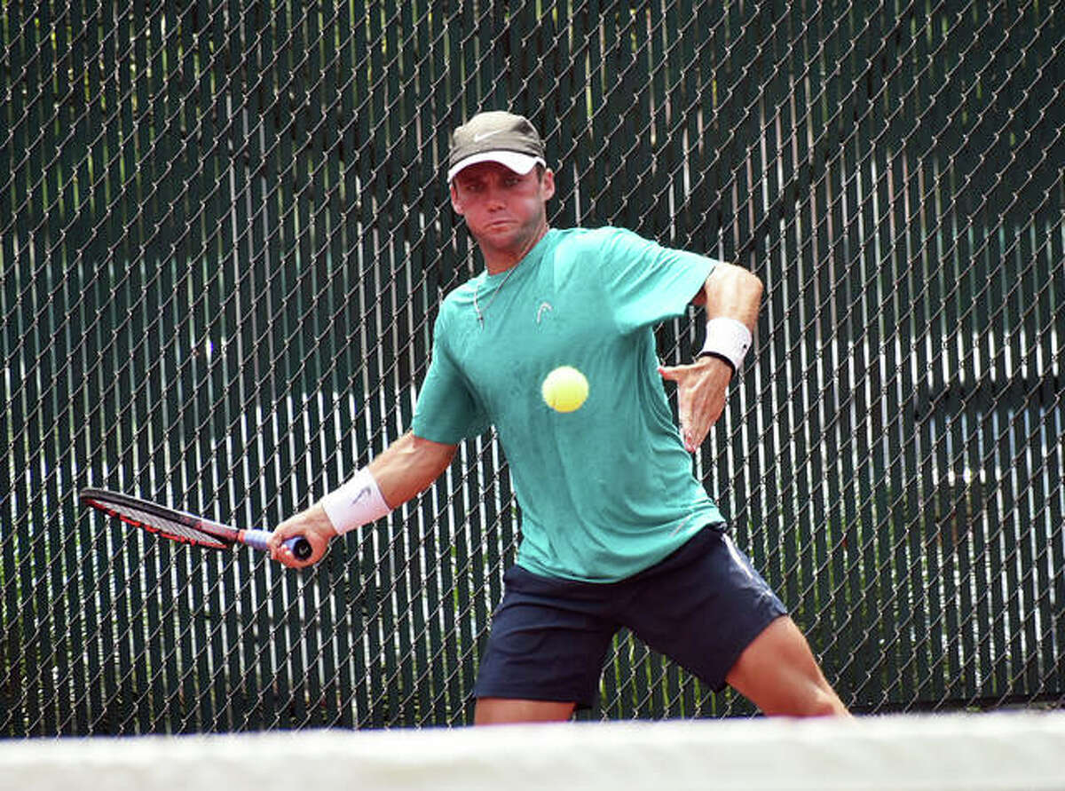 Zeke Clark hits a return shot during doubles match with partner Alex Brown in the second round of the Edwardsville Futures tennis tournament.