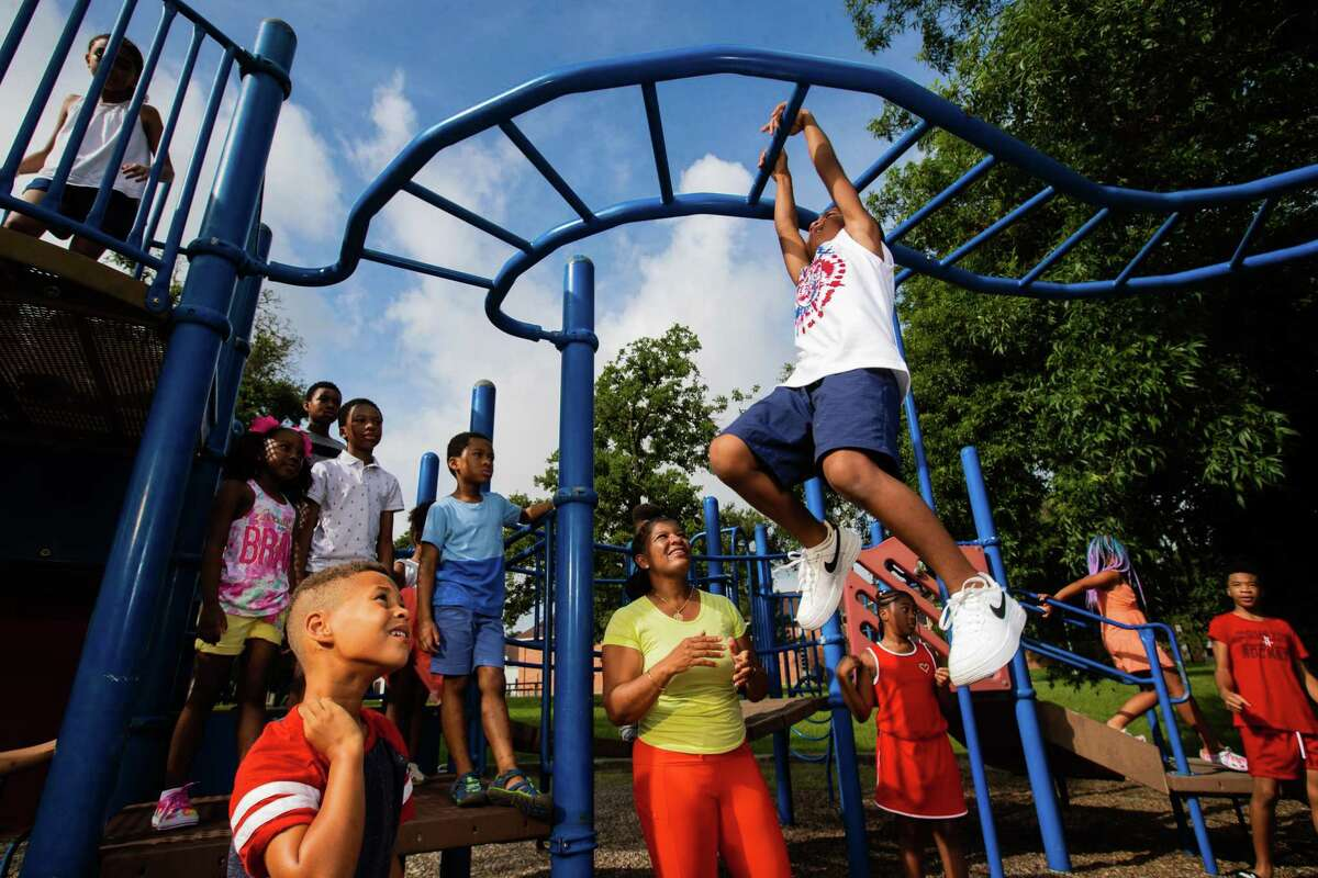 Friends of Riverside Park Houston president Sharon Evans Brooks, center, enjoys time with children at the Third Ward park.