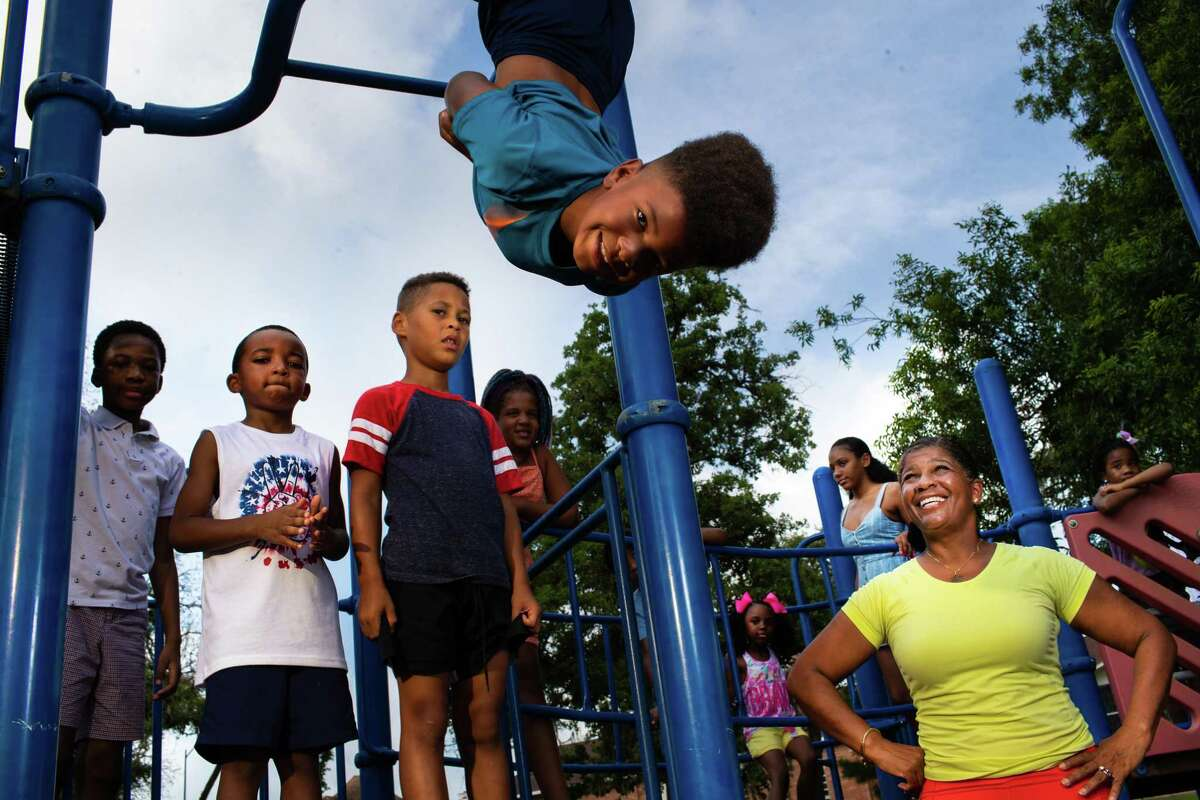 Friends of Riverside Park Houston director Sharon Evans Brooks, center, takes a look as children who are members of Third Ward community play during a portrait session at the Riverside Park, Monday, July 19, 2021, in Houston.