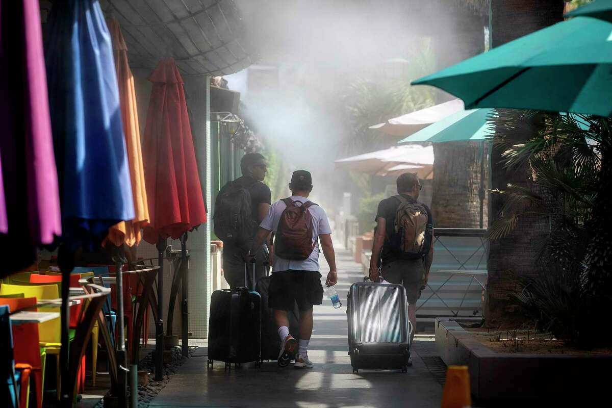 Tourists pull their luggage under cooling misters in 110-degree temperatures on July 8, 2021, in downtown Palm Springs, California. (Gina Ferazzi/Los Angeles Times/TNS)