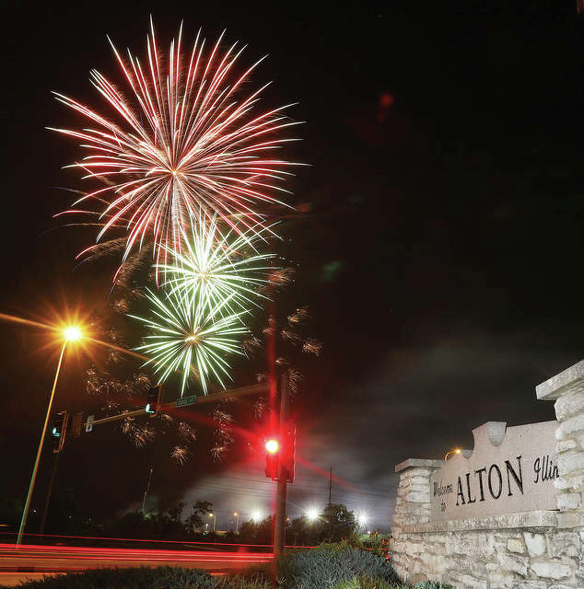 Fireworks explode over the Alton riverfront Thuirsday night as seen from the corner of Ridge Street and Landmarks Boulevard in Alton. Fireworks were also going off in Grafton at the Lighthouse Park thanks to the Great Rivers and Routes Tourism Bureau of Sothwestern Illinois.