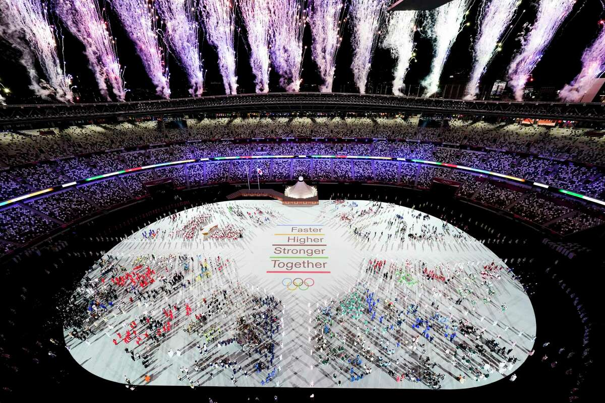 Athletes are seen with fireworks during the opening ceremony at the Olympic Stadium at the 2020 Summer Olympics, Friday, July 23, 2021, in Tokyo.