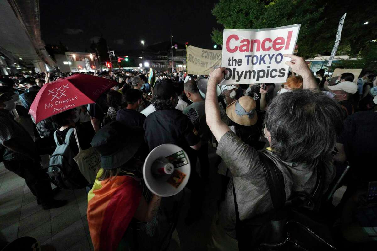 Anti-Olympic protestors demonstrate near the National Stadium in Tokyo, Japan where the opening ceremony of the Tokyo Olympics took place, Friday, July 23, 2021. (AP Photo/Kantaro Komiya)
