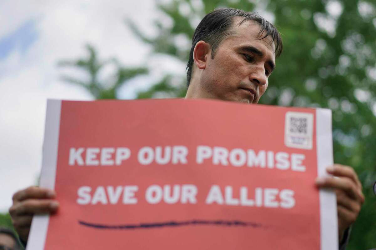 """Abdul Wahid Forozan, a former translator for the American military in Afghanistan, holds a sign that reads """"Keep Our Promise Save Our Allies"""" near the White House in Lafayette Square Park in Washington on July 1 during a rally hosted by the International Refugee Assistance Project, Human Rights First, and With Honor Action, to call for the evacuation of Afghan allies."""