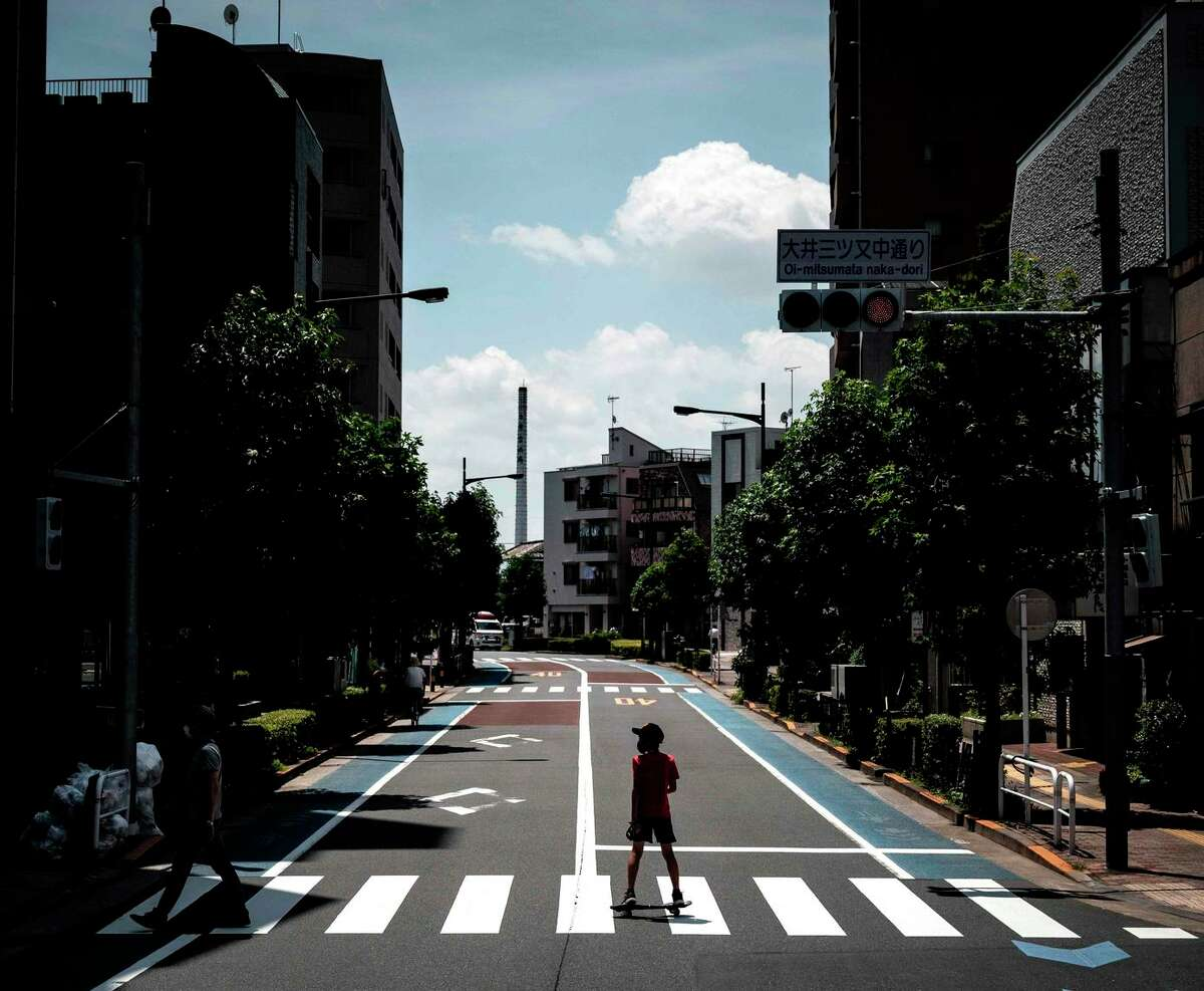 A child rides a skateboard on a Tokyo street, as seen from an Olympic media bus, earlier this week. Media and athletes are not allowed to mix with the Japanese public.