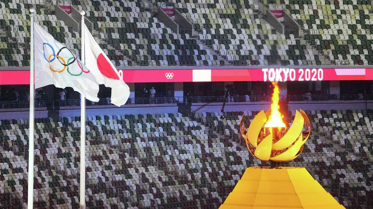 The Olympic fire burns next to the Olympic and Japanese flags during the opening ceremony.