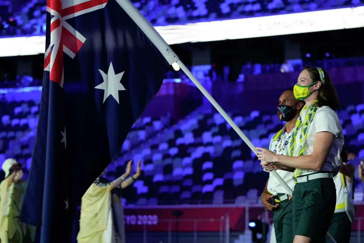 Cate Campbell and Patty Mills, of Australia, carry their country's flag during the opening ceremony in the Olympic Stadium at the 2020 Summer Olympics, Friday, July 23, 2021, in Tokyo, Japan. (AP Photo/Natacha Pisarenko)
