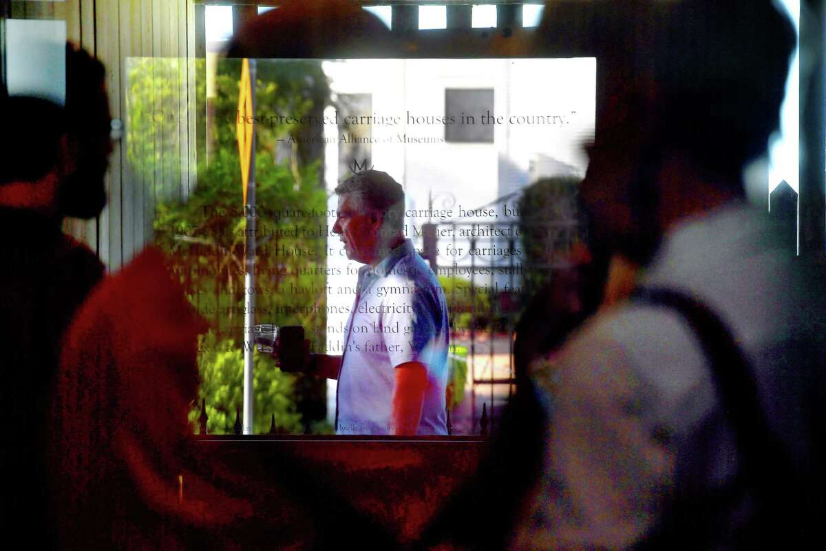 Guests are reflected in glass as some socialize while others take guided tours during Heritage Happy Hour Thursday at the McFaddin-Ward House Museum's carriage house. Photo made Thursday, July 22, 2021 Kim Brent/The Enterprise