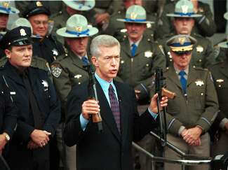 California Gov. Gray Davis holds up an AK-47-style assault rifle that was cut into two pieces before his signing of SB23, the assault weapons bill, in July 1999. In the background are members of the California Highway Patrol and San Francisco Police Department.