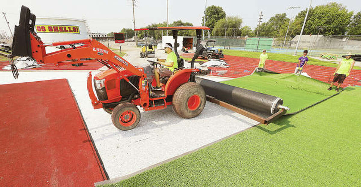 A tractor unrolls another strip of artificial turf Wednesday at the Charles Raich Football Field at Roxana High School. Work is nearing the final stages on the football field but prep work is still underway at the nearby soccer field which will also have artificial turf.