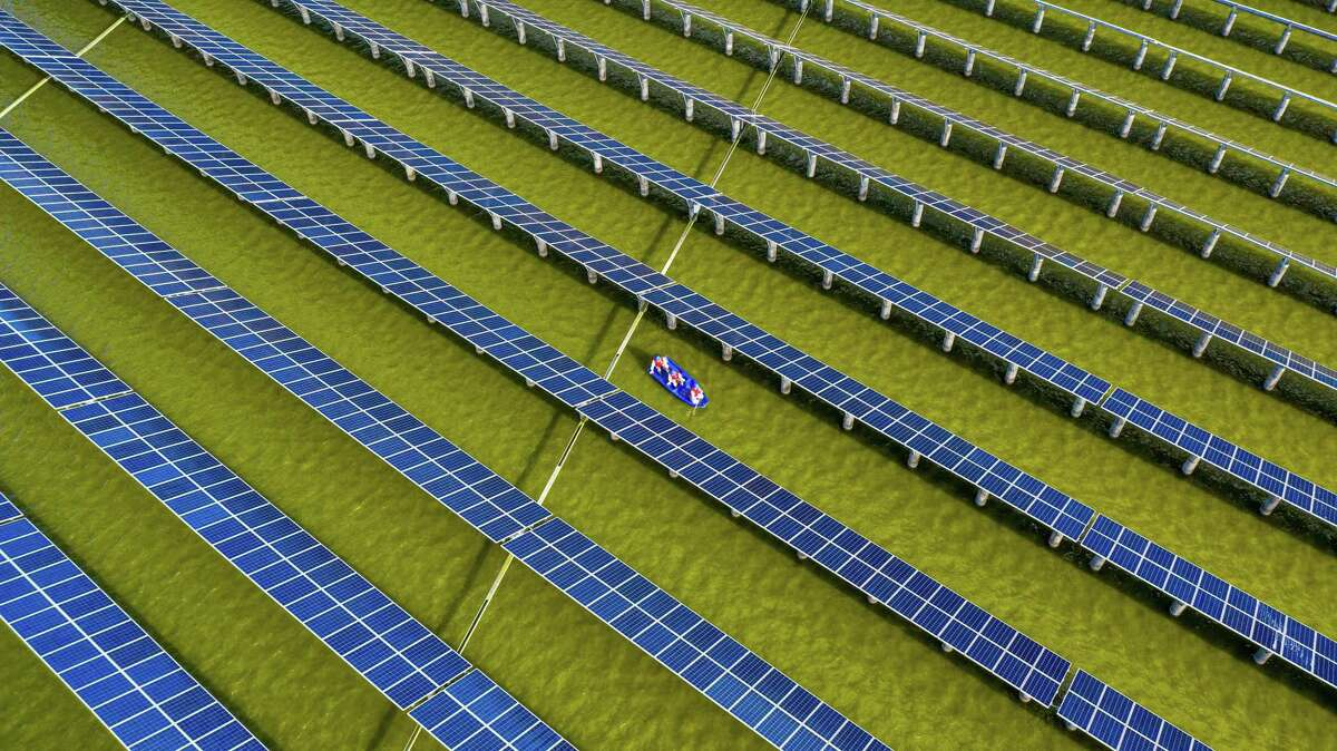 Electrical workers in a boat check solar panels Monday at a photovoltaic power station built in a fishpond in Haian in China's eastern Jiangsu province.