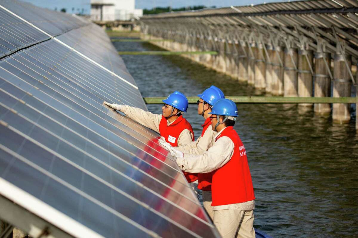 Above, workers check solar panels Monday at a power station built in a fishpond in Haian, in China's eastern Jiangsu province.