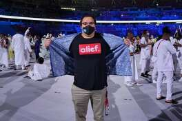 Shawn Dingilius Wallace, a swimmer representing Palau in the Olympics, showed off his Alief T-shirt at the opening ceremony Friday, July 23, 2021 at Tokyo's Olympic Stadium.