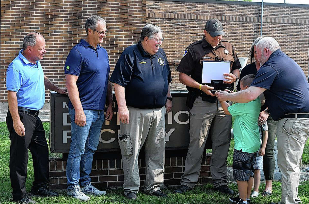 Morgan County Sheriff's deputy Derek Suttles (center) receives the FOP Meritorious Service Award on Friday at Morgan County Sheriff's Office from his son Paxton and Illinois FOP State Lodge President Chris Southwood (right). Morgan County Sheriff Mike Carmody (from left); Chief Deputy Jamie Jackson; FOP awards chair Jerry Lieb; and Suttles' family, including his wife, Chelsea, and son Croy; were on hand for the presentation.