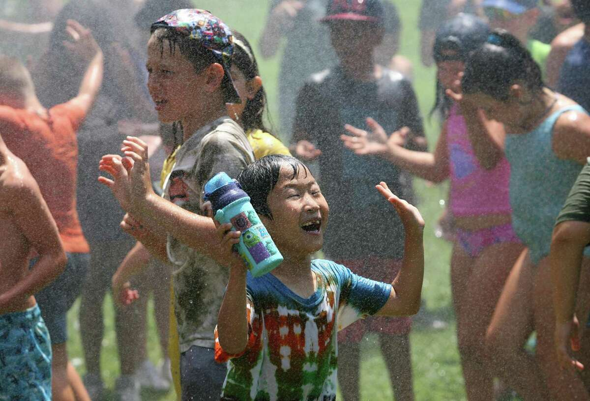 Tomohiro Shimba, 8, enjoys cooling off as Santa sprays him and his friends with a firehose during at Camp Simmons in Greenwich, Conn., on Friday July 23, 2021.