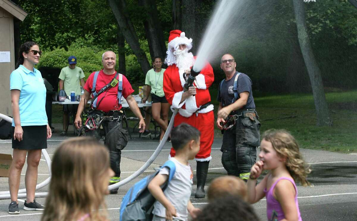 Santa douses children with a firehose during the Boys and Girls Club of Greenwich summer camp's annual Christmas in July tradition at Camp Simmons in Greenwich, Conn., on Friday July 23, 2021.
