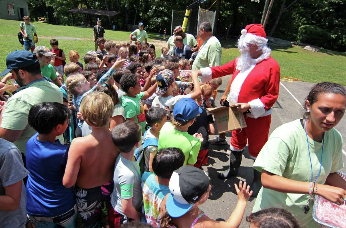 Santa hands out candy canes after arriving on a firetruck during the Boys and Girls Club of Greenwich summer camp's annual Christmas in July tradition at Camp Simmons in Greenwich, Conn., on Friday July 23, 2021.After handing out the candy, a firehose was used to cool the kids off.