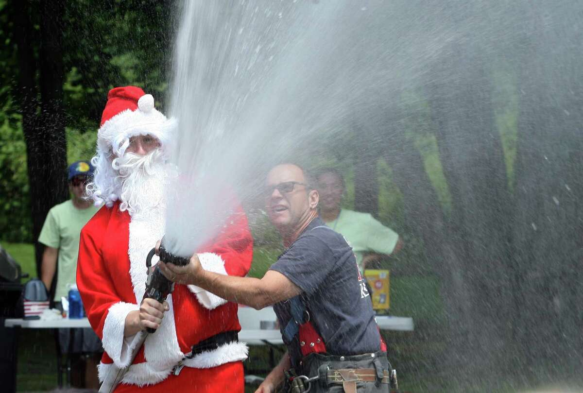 Santa cools off the kids after arriving on a firetruck during the Boys and Girls Club of Greenwich summer camp's annual Christmas in July tradition at Camp Simmons in Greenwich, Conn., on Friday July 23, 2021.