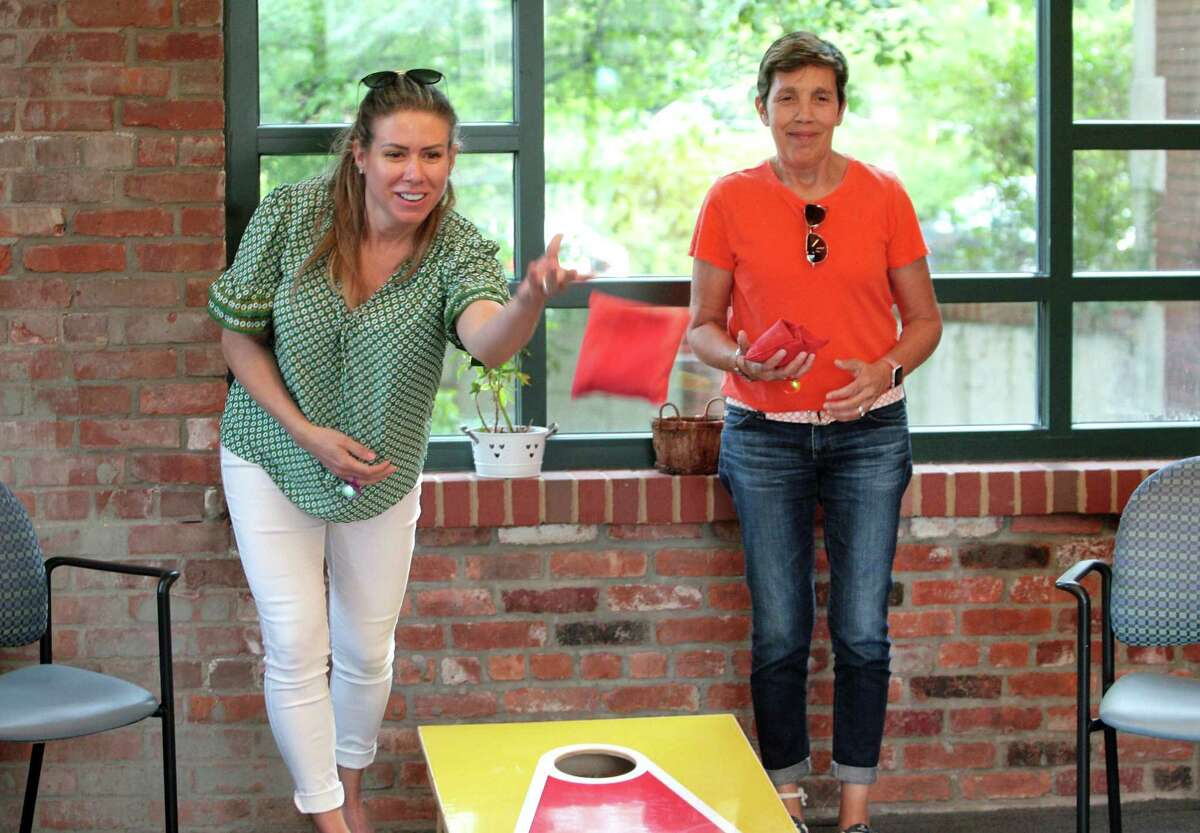 """Jill Cofrancesco, left, and Christina Crain play a game of cornhole during River House Adult Day Center's """"Game On"""" party/fundraiser in Cos Cob, Conn., on Thursday July 22, 2021. The event featured an evening of summer fun, live music and games, along with a silent auction cold beer, wine or hard seltzer. All proceeds will benefit River House?s """"Fund-A-Client"""" scholarship fund."""